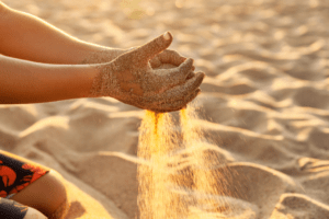 child's hands playing in the sand