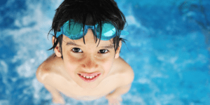 boy in a pool looking up at camera