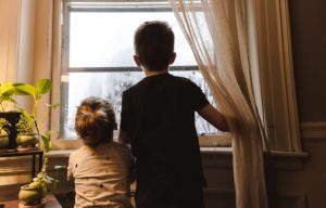 two kids looking out a window