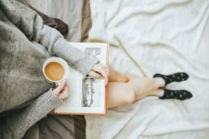photo of a woman's torso and legs reading a book and drinking coffee