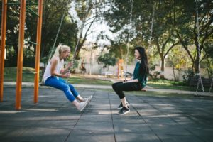 two women facing each other on swings and laughing together