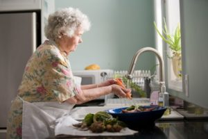 elderly woman with short white curly hair washing vegetables at the sink near the window