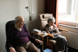 elderly couple sitting side by side in a residential care facility