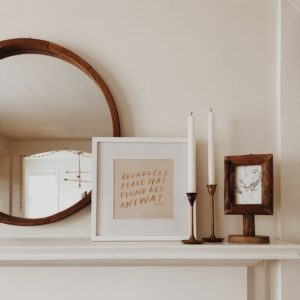 picture of a mantle with a few wooden and white decorations