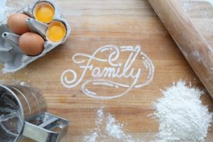 "top view of messy countertop with the word ""family"" spelled in white like flour"
