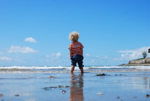 picture of a toddler boy wading into the ocean looking away from the camera