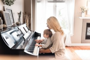 mom holding toddler son and playing piano together