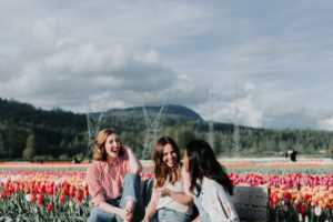 3 women laughing together on a bench in front of a field of colorful tulips