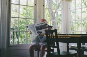 elderly man sitting at a kitchen table reading a newspaper in a sunny room full of windows