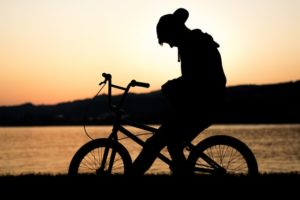 silhouette of a teenage boy at sunset on his bike looking down