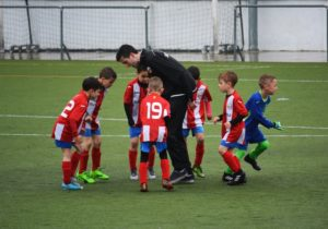picture of a team of young soccer players and their coach on the field in a huddle
