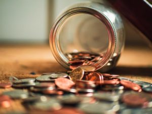picture of a jar of pennies and coins spilling out of a jar