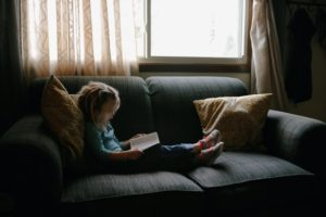 picture of a little girl reading a book on the couch near a window
