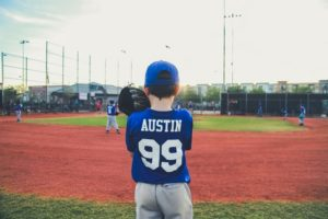 picture of the back of a boy on a baseball field getting ready to pitch a ball