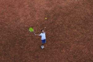 overhead picture of a boy throwing a tennis ball up in the air getting ready to hit it